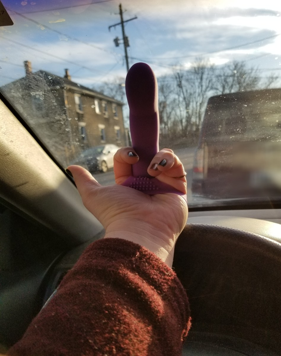 An arm in a car that can be seen with the Extra touch over the middle finger. It looks as if they are flicking off other drivers.