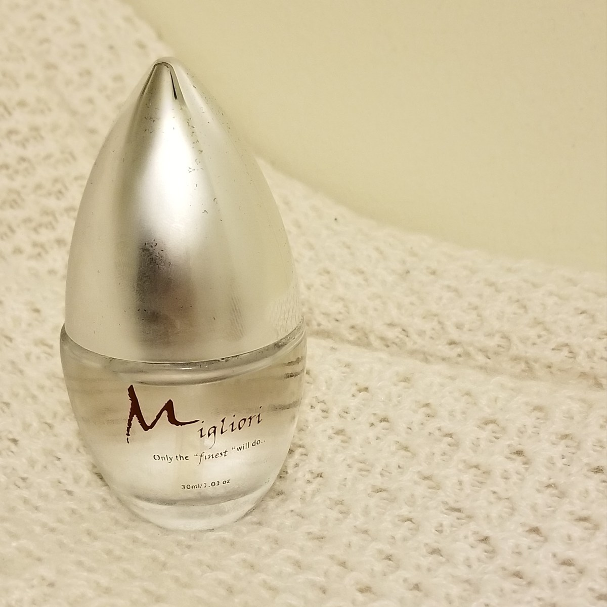 A glass bottle with a silver top sits on a knitted fabric. There is Migliori written on the bottle in a fancy font.