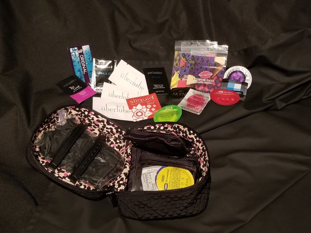 There is a black Sheets of San Francisco Funsheet spread out. On top is a collection of lube samples, condoms, dental dams. There is a small black make-up case next to them, which is opened to reveal black of black gloves and more condoms.