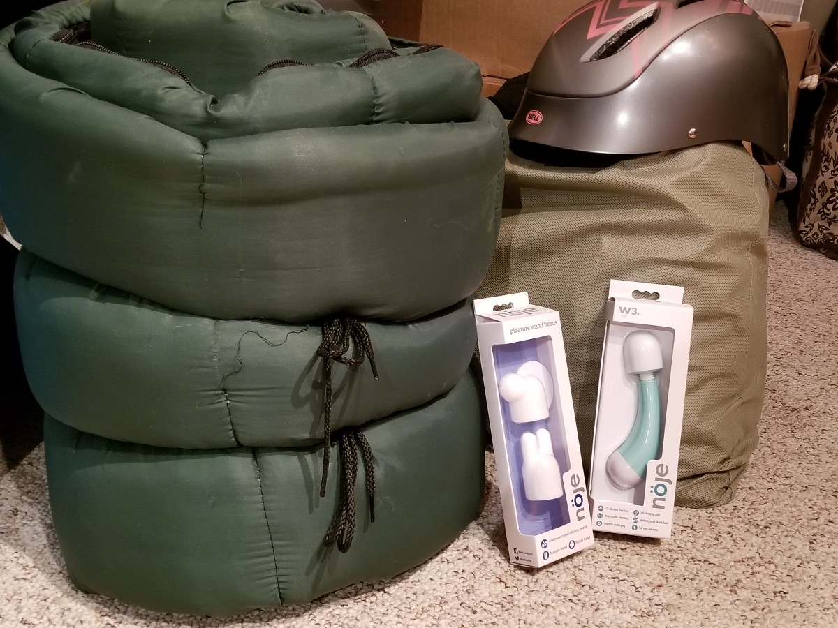 The Noje W3 Wand and the Noje W3 Wand attachments are sitting in their boxes next to a packed green bag, a green sleeping bag and a bicycle helmet. There is further description of the toy in the next image and in the post.