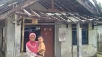 Mariam, janda 50 tahun saat menggendong anak bungsunya di teras rumah miliknya yang dalam keadaan rusak, Selasa (16/1/21).