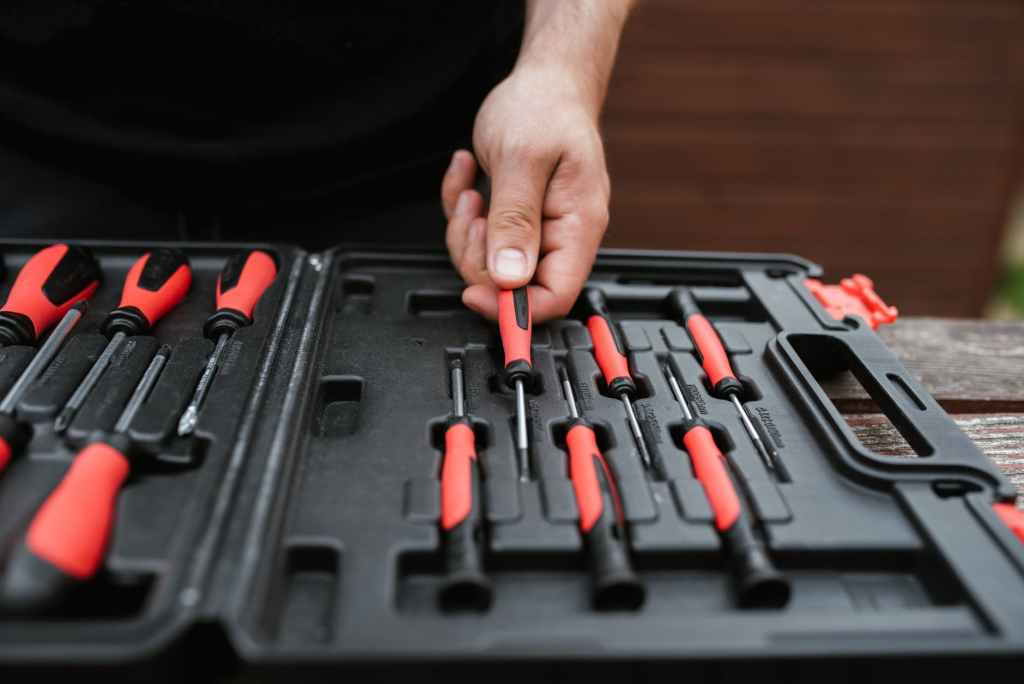 faceless master choosing screwdriver from toolbox