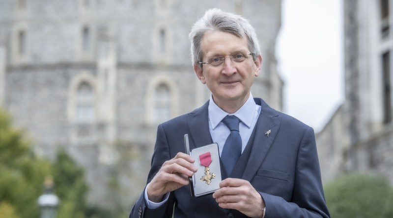 Dr. Jim Beveridge with his OBE award outside Windsor Castle