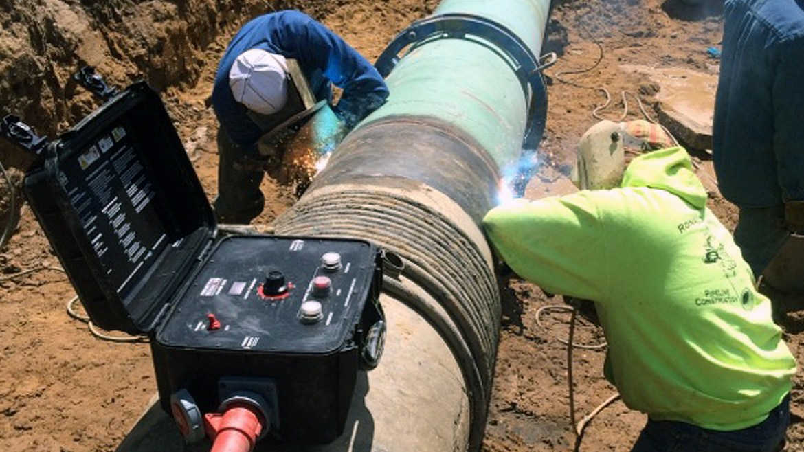 Services header image. Two people using special equiment to demagnetize a pipe.