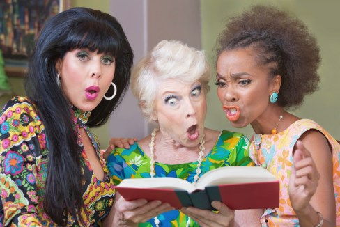 Three women look at a book, scandalized.