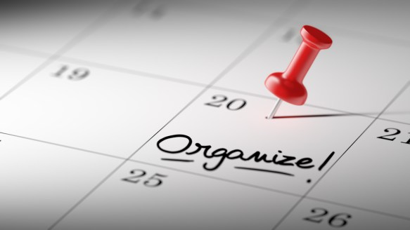 "A red pin pressed into a calendar day where ""organize!"" is written."