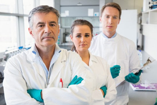 Three scientists look into the camera, displeased.