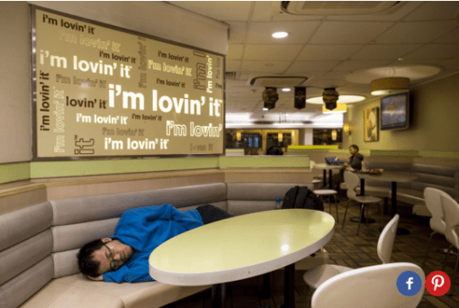 A homeless person sleeps on a booth in a McDonald's restaurant.