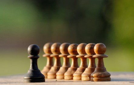 A line of pale chess pieces face a dark-colored one.