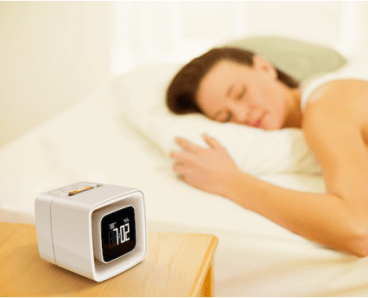 A woman sleeps happily in bed with a Sensorwake alarm clock on her nightstand.