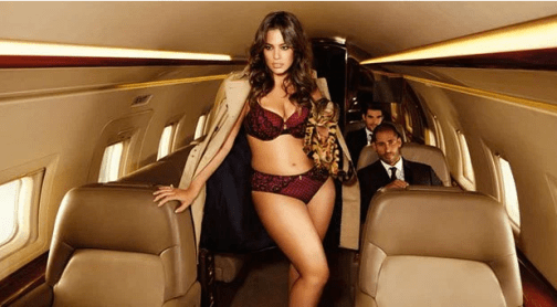 Ashley Graham models in underwear on a plane.