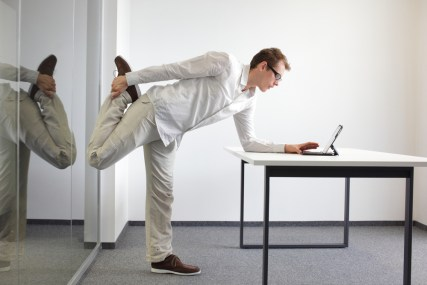 A man stretches while using his phone at work.