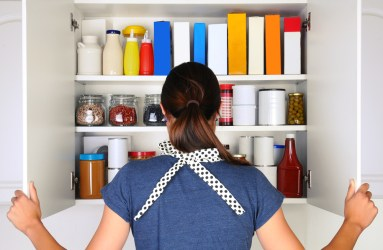 A woman peeks into a food pantry.