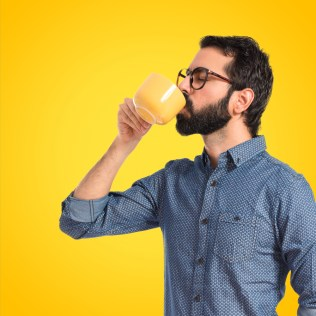A man happily drinks coffee from a mug over a yellow background.
