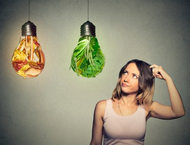 A woman considers whether to eat lettuce or junk food.