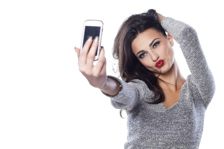 A photo of a young, attractive woman taking a selfie picture.
