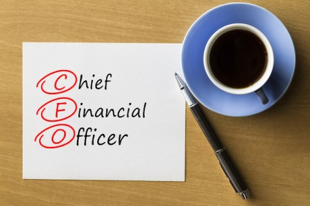 """A cup of coffee and a piece of paper that reads """"chief financial officer."""""""