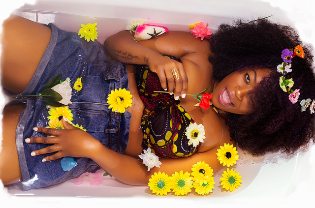 Upcoming singer D'vyne in a bathtub with flowers and curly Afro hair