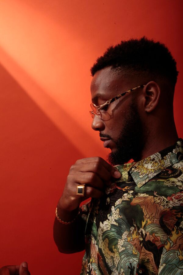 British producer and artist footsteps in a multicoloured patterned shirt against a red backdrop