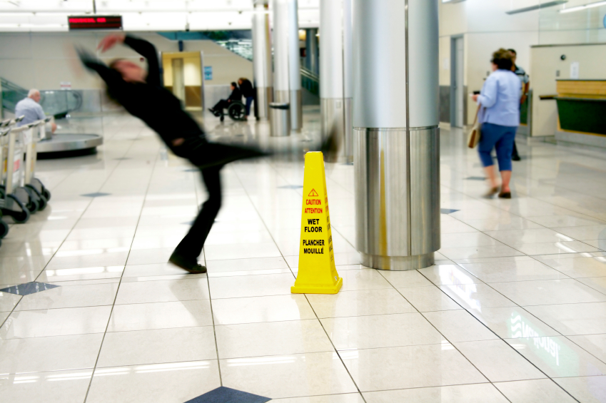 Man slips next to Wet Floor sign