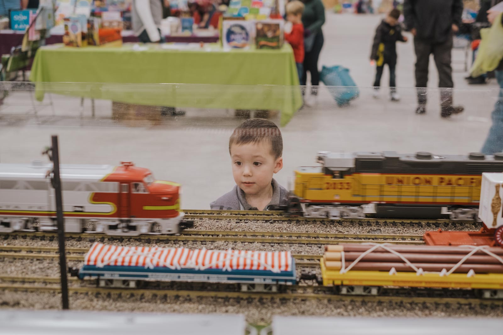 A small on looker enjoys the passing trains.