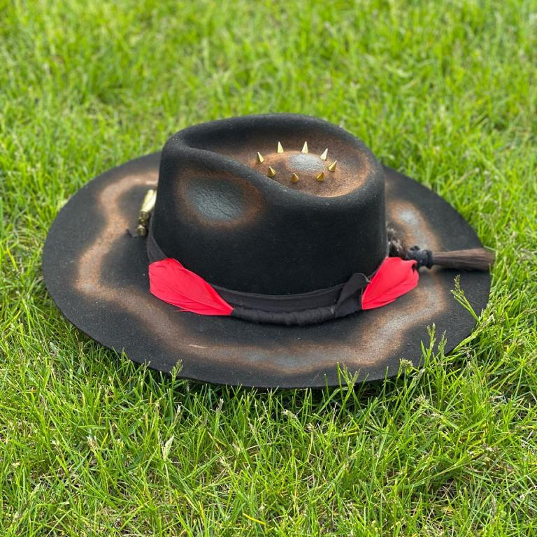 Black custom hat with red feathers and studs