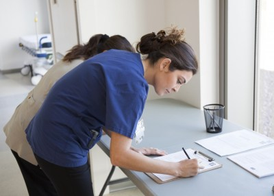 Marcela Delatone and her colleague sign consent forms to receive the influenza vaccination at Palomar Health, Sept. 21, 2015. Megan Wood, inewsource