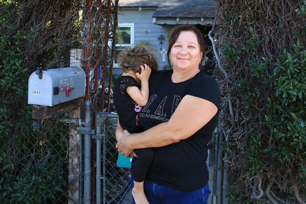 Katherine LeMoine stands outside her home holding her niece on Oct. 8, 2015. Megan Wood, inewsource.