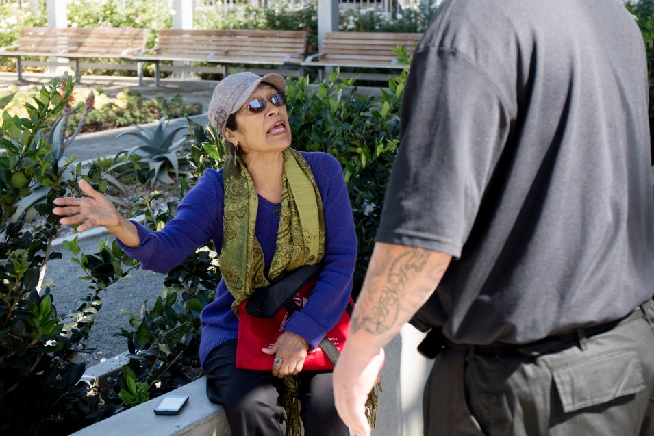 Patricia Botello, a resident of East Village, speaks to a security guard at Fault Line Park. She said too often she sees homeless people drinking, doing drugs and using the park itself as a bathroom. Megan Wood, inewsource. Oct. 5, 2016.