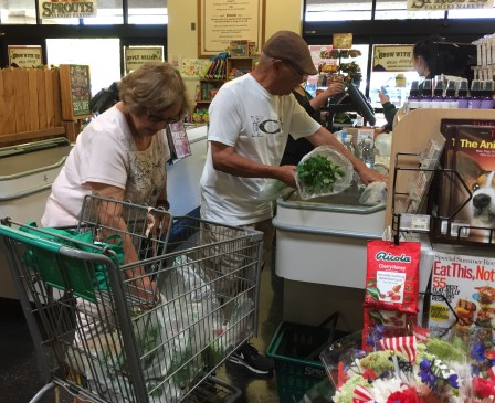 Teri and Oscar Lara load their healthier grocery items at the Sprouts checkout. Both have lost weight since they began watching what they eat. June 27, 2017. Cheryl Clark, inewsource