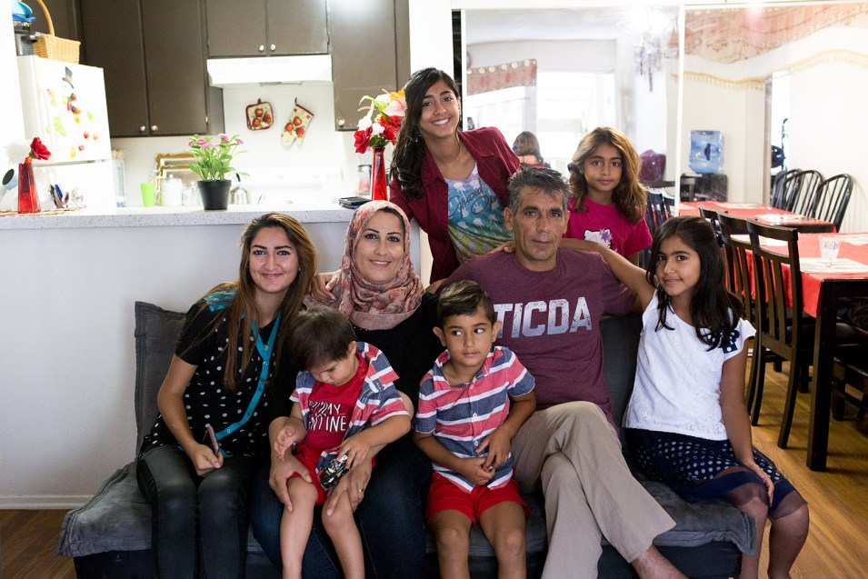 Daliya Ail, center, and her husband, Salim Musa, pose with their six children in their two-bedroom El Cajon apartment, July 25, 2017. Photo by Megan Wood, inewsource.