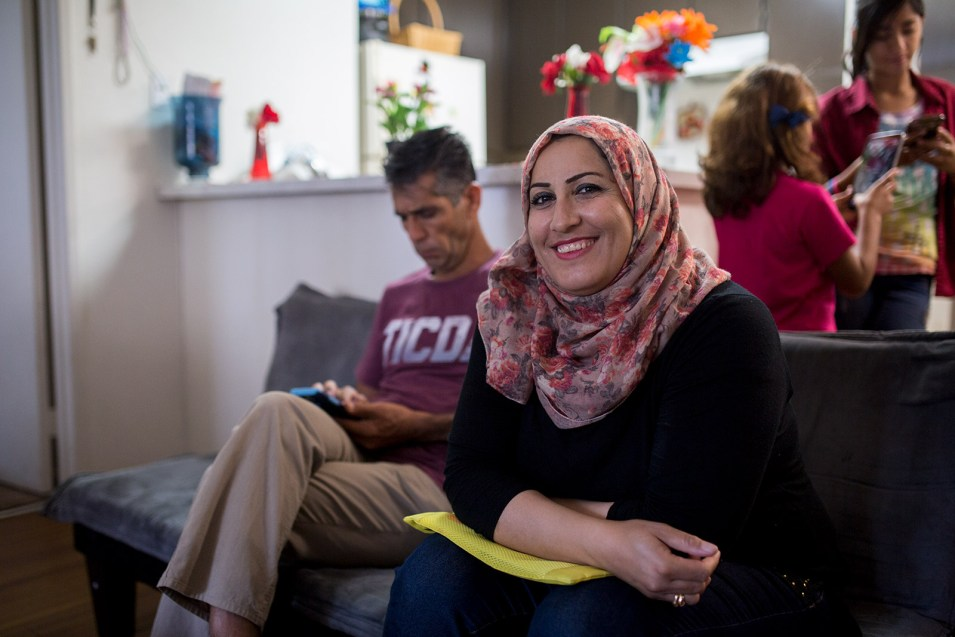 Daliya Ali smiles while sitting alongside her husband in the living space of their El Cajon apartment, July 25, 2017. Photo by Megan Wood, inewsource.