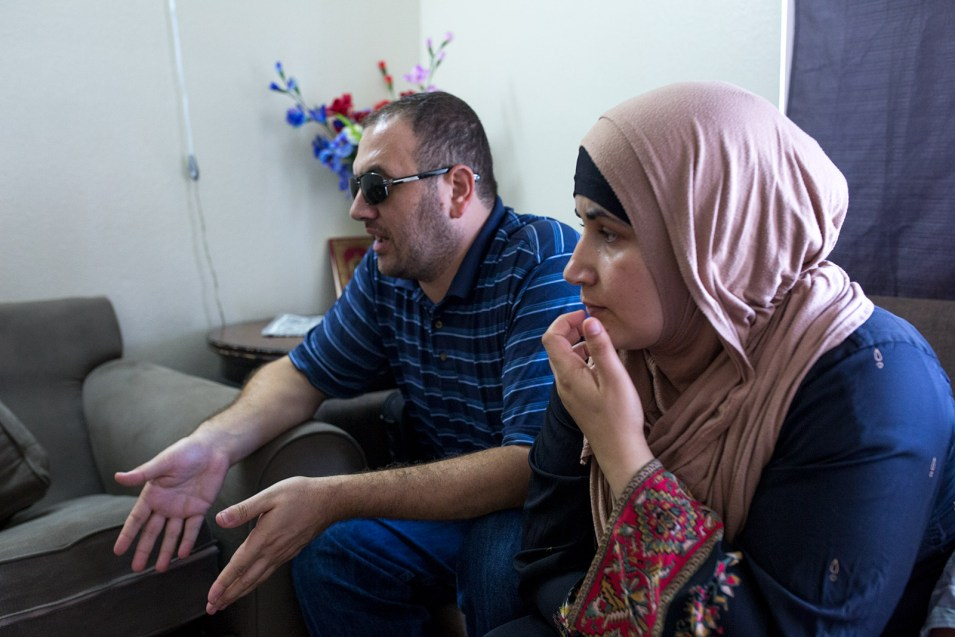 Mostafa Inezan, (left) and his wife, Waelah, speak with a family friend (not pictured) while sitting on a couch in the family's new three-bedroom apartment, July 25, 2017. Photo by Megan Wood, inewsource.