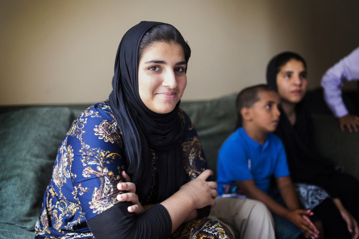 Saadia Hamdard, an Afghanistan refugee, sits on the couch in her family's two-bedroom apartment in El Cajon, Aug. 1, 2017.