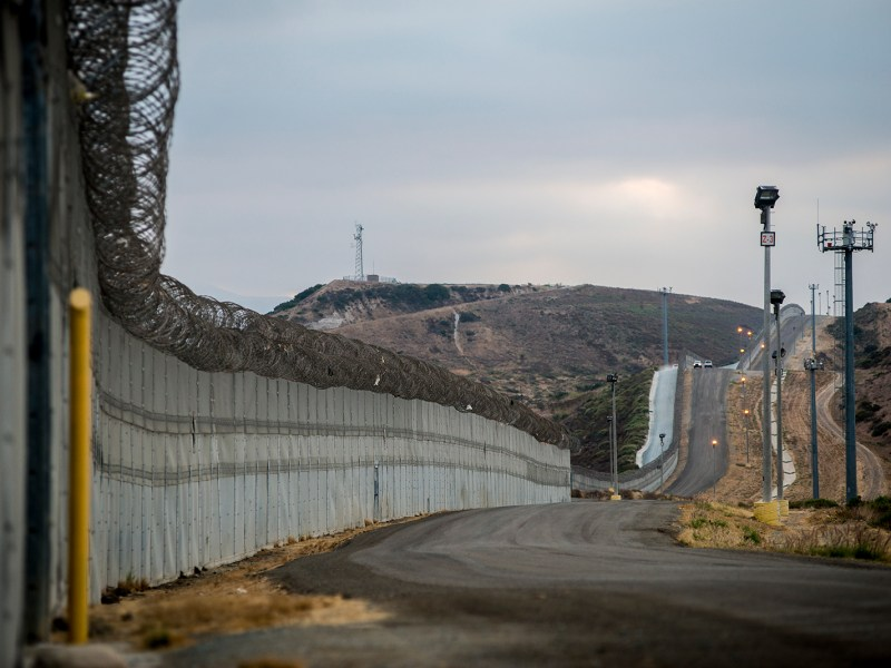 Stretches of secondary fencing are topped with spirals of concertina wire along the U.S.-Mexico border between the San Ysidro and Otay Mesa ports of entry, in San Diego on Aug. 16, 2017. Border Patrol agents use the frontage road between this and primary fencing to patrol for immigrants attempting to enter the U.S. illegally. (Brandon Quester/inewsource)