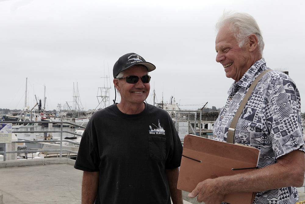 Commercial fishermen David Haworth (left) and Peter Halmay talk on the G Street Mole on Sept. 24, 2018. (Brad Racino, inewsource)
