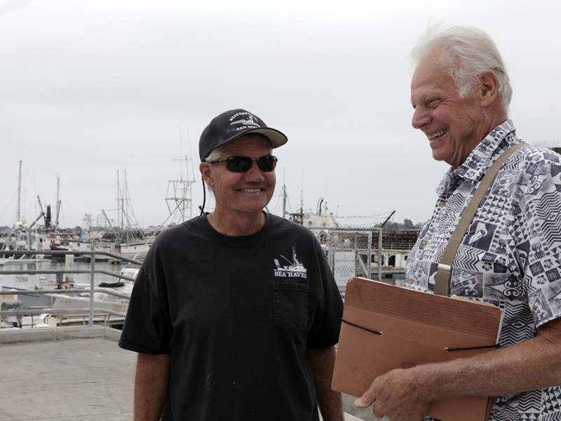 Commercial fishermen David Haworth (left) and Peter Halmay talk on the G Street Mole on Sept. 24, 2018. (Brad Racino, inewsource)