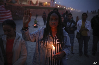 A woman holding a candle observes a minute of silence in memory of migrants who have died during their journey toward the U.S., near the border fence that separates Mexico from the U.S., in Tijuana, Mexico, June 29, 2019.