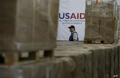 A man walks past boxes of USAID humanitarian aid at a warehouse at the Tienditas International Bridge on the outskirts of Cucuta, Colombia, Feb. 21, 2019, on the border with Venezuela. Venezuela's President Nicolas Maduro said he's weighing whether to shut down the border with Colombia, where the bulk of aid meant for Venezuela is being stockpiled and exiled leaders have been gathering ahead of a fundraising concert Friday. (AP Photo/Fernando Vergara)