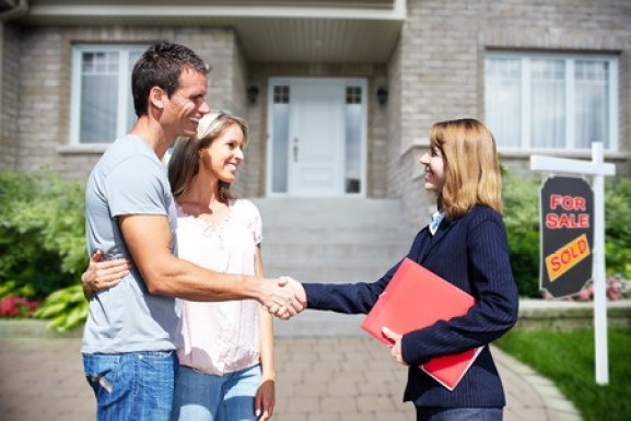 Buyers agent shaking hands with their client outside of a house.
