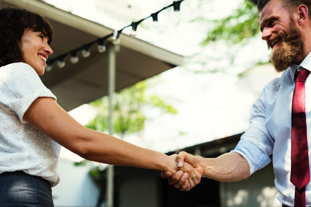 transaction coming to an agreement. The seller, a woman, is shaking hands with the buyer, a bearded man. Why you should negotiate directly.