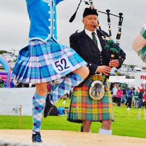 Highland dancers wearing kilts with bagpiper