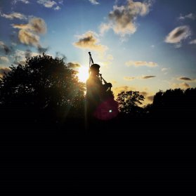 A bagpiper is silhouetted against the evening sun