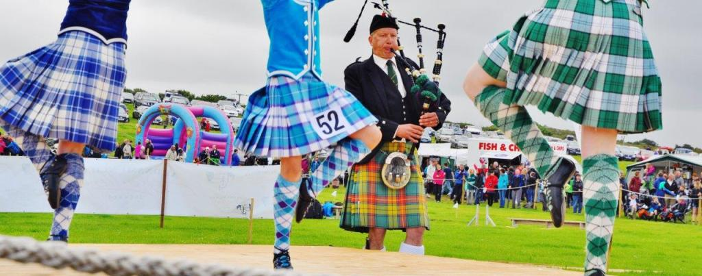 Bagpiper with Highland dancers in tartan kilts