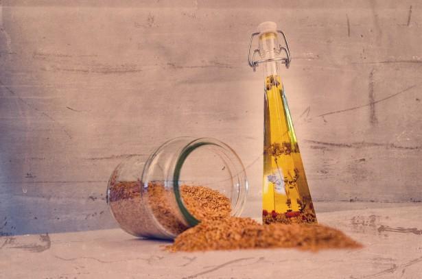 huile de sésame avec un pot de sésame broyer renversé