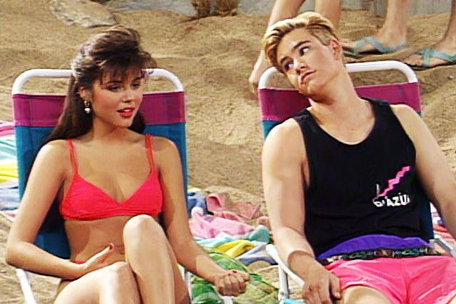 Kelly and Zach from Saved by the Bell sitting on the beach in their very 80s swimwear
