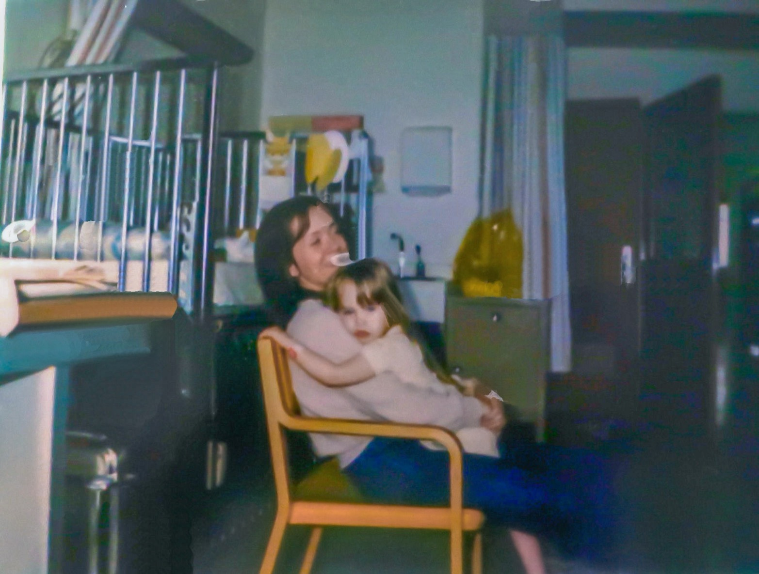 Laying on my mom's lap while she sits in a chair with her arms around me in the hospital. My hospital bed behind us. I was about age 4
