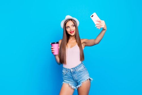 Nice winsome adorable attractive cheerful positive straight-haired girl, hipster wearing cap, shorts, tanktop, holding take-out coffee, taking self-photo, isolated over bright vivid blue background