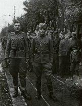 Два офицера НОАЮ стоят перед своими бойцами.