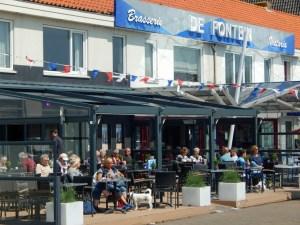 Touristen sitzen auf Terrasse einer Brasserie in Westkapelle